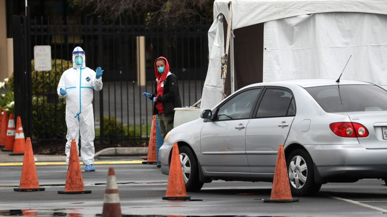 SAN MATEO, CALIFORNIA - MARCH 16: A medical worker guides a car that is going through a coronavirus drive-thru test clinic at the San Mateo County Event Center on March 16, 2020 in San Mateo, California. Drive-thru test clinics for COVID-19 are popping up across the country as more tests become available. (Photo by Justin Sullivan/Getty Images)