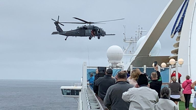 Passengers on the Grand Princess watch a helicopter land as it delivers coronavirus testing kits