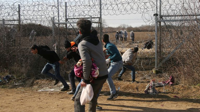 Migrants throw stones at a Greek military vehicle on the Turkish-Greek border at Turkey's Pazarkule border crossing with Greece's Kastanies