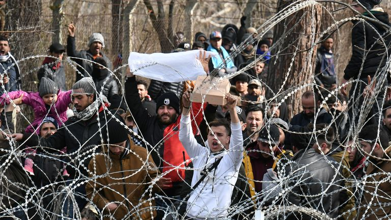 Migrants who want to cross into Greece from Turkey's Pazarkule border crossing shout slogans as they are gathered at the borderline in Kastanies