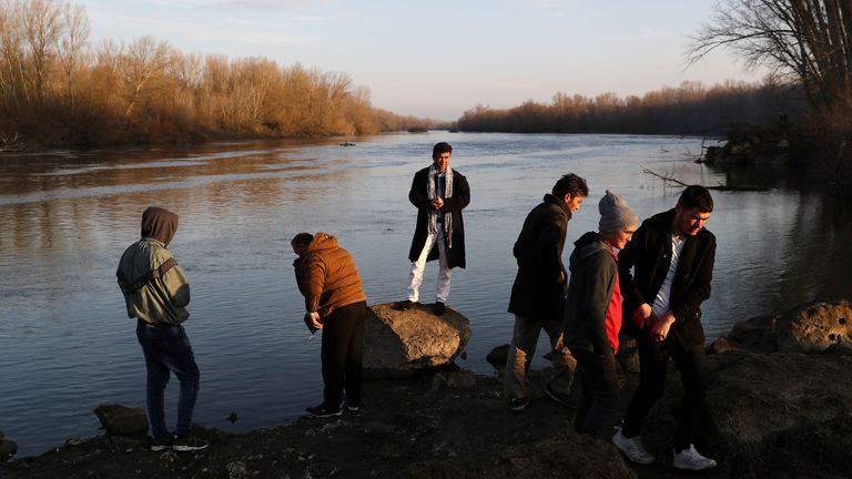 Migrants stand on the banks of Evros river, natural border between Turkey and Greece, near Edirne, Turkey