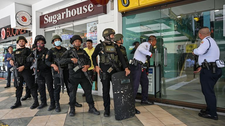 Members of a police SWAT team prepare to enter a mall after a hostage situation was reported in suburban Manila