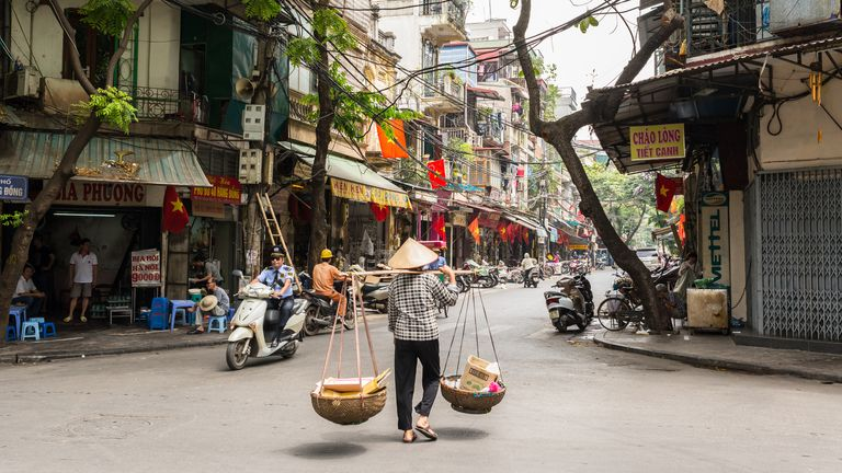 A street vendor transporting goods in baskets in Hanoi's Old Quarter