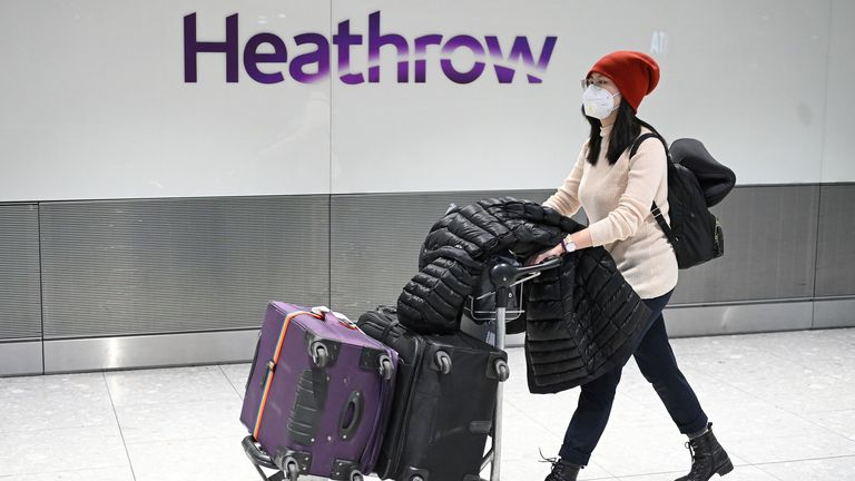 Passengers wear face masks as the push their luggage after arriving from a flight at Terminal 5 of London Heathrow Airport in west London on January 28, 2020 (File pic)