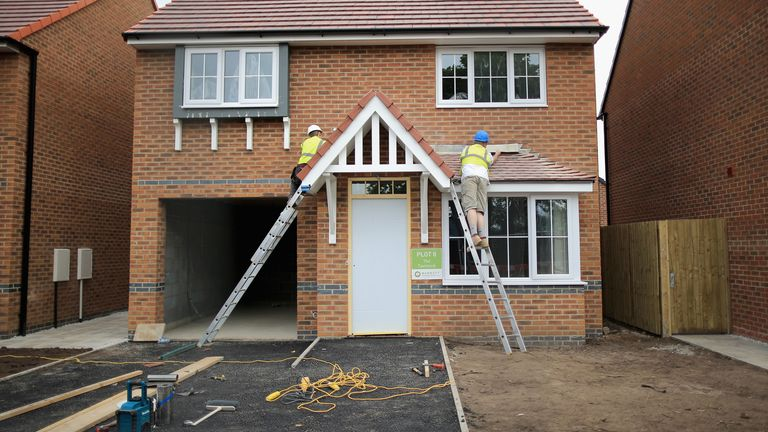 Construction workers build new houses on a housing development on May 20, 2014 in Middlewich, England