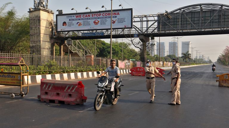 Police officers try to stop a motorcyclist at a barrier in India