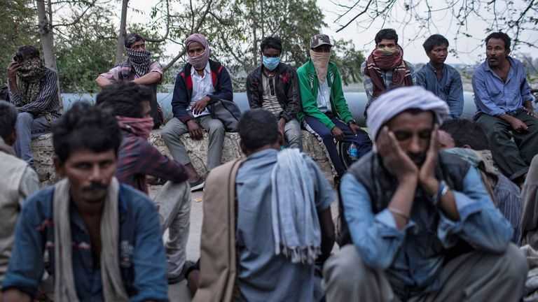 Daily wage workers and homeless people wait for food outside a shelter in Delhi