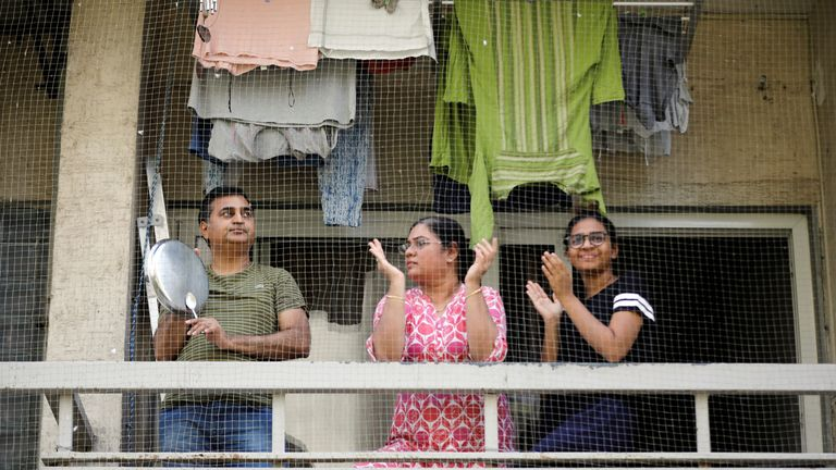 Residents clap and bang utensils from their balcony to cheer for emergency personnel and sanitation workers who are on the frontlines in the fight against coronavirus