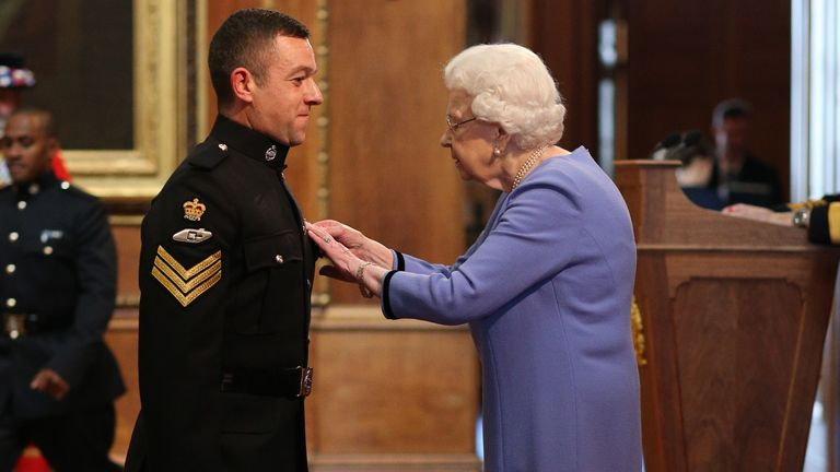Staff Sergeant Stuart Griffiths is decorated with the Queen's Gallantry Medal by Queen Elizabeth II at Windsor Castle.