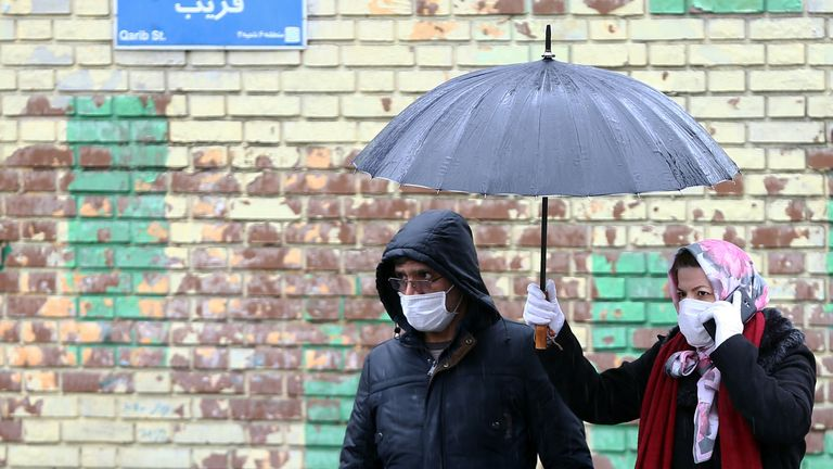 Iranian people wear protective masks to prevent contracting coronavirus, as they walk in the street in Tehran, Iran February 25, 2020