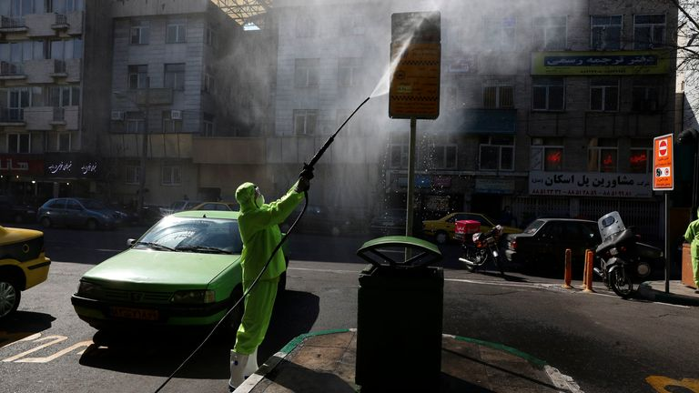 A city worker disinfects a bus stop sign because of the new coronavirus in Tehran, Iran, Thursday, March 5, 2020. Iran has one of the highest death tolls in the world from the new coronavirus outside of China, the epicenter of the outbreak. (AP Photo/Vahid Salemi)