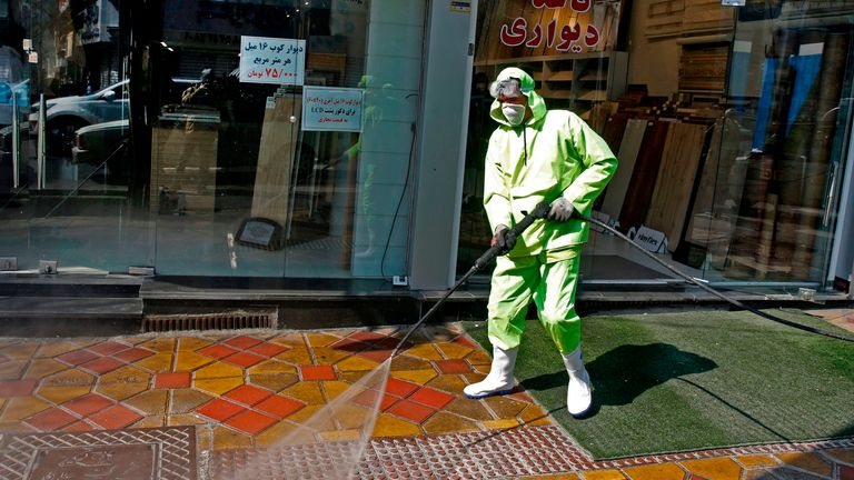 Iranian workers disinfect a street in Tehran