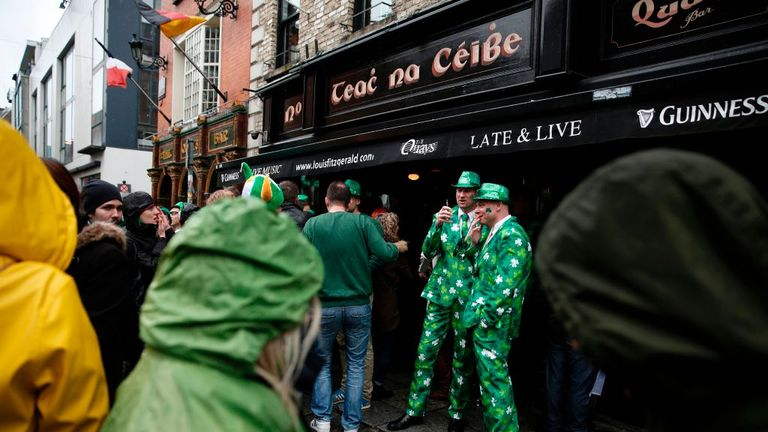 Tourists stand outside a pub in Temple Bar during the St. Patrick's Day parade in Dublin, Ireland on March 17, 2017. / AFP PHOTO / ADRIAN DENNIS (Photo credit should read ADRIAN DENNIS/AFP via Getty Images)