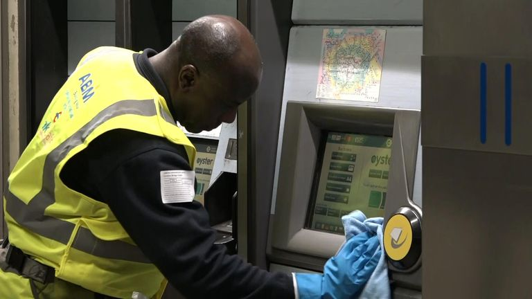 A man is seen cleaning an Oyster card machine at a tube station in the capital