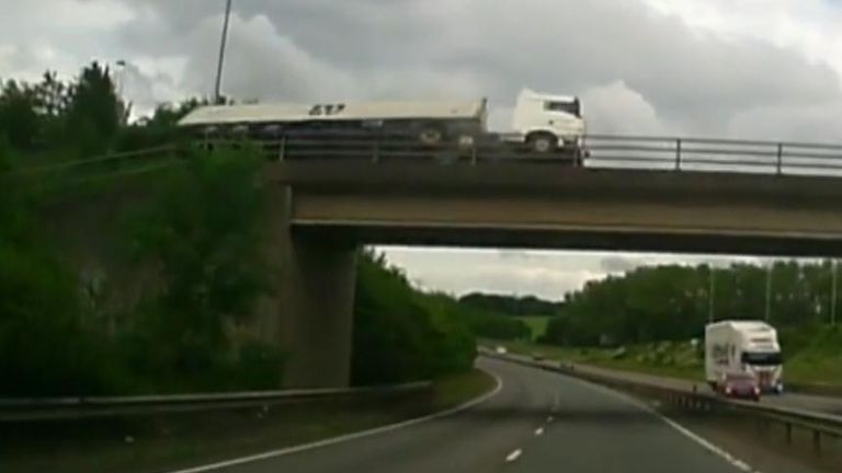 The lorry was left hanging precariously over a dual carriageway after tipping over on a bridge