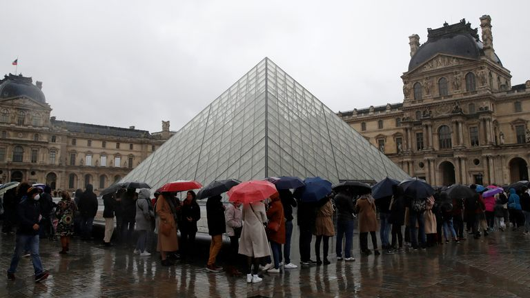 People line up outside the Louvre in Paris as staff closed the museum during a staff meeting over coronavirus