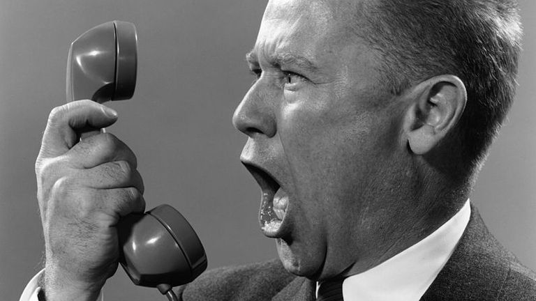 circa 1955: A businessman wearing a suit shouts into a telephone. (Photo by Lambert/Getty Images)