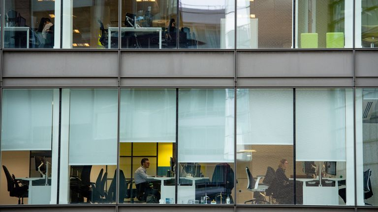 Office workers in Manchester sit amongst empty chairs
