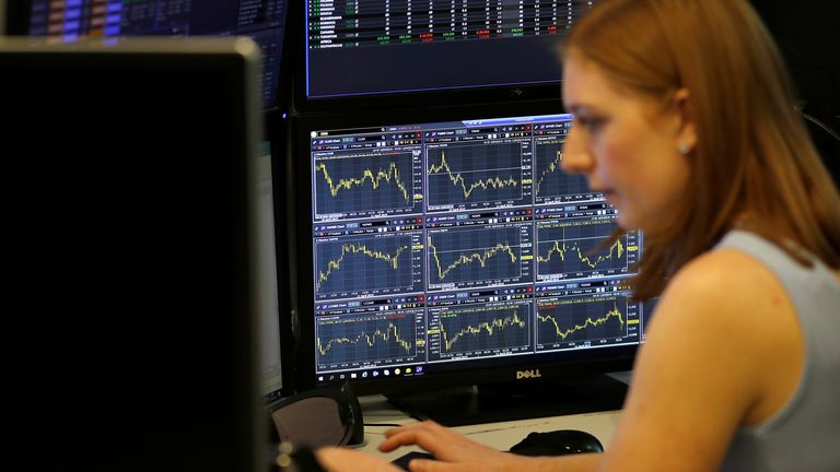 A financial trader works at their desk at CMC Markets in the City of London, Britain, April 11, 2019