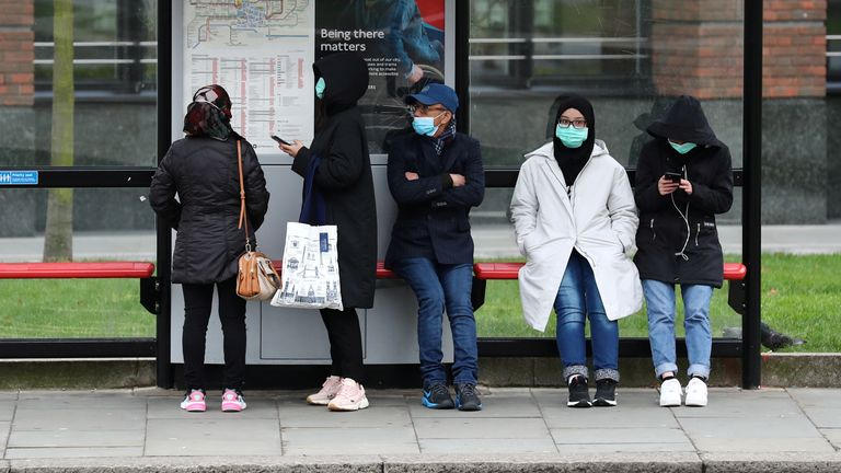 People in masks wait for a bus in central London