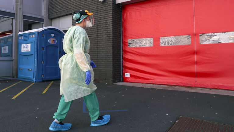A medic wears a protective mask and suit at a hospital in Aalst, Belgium