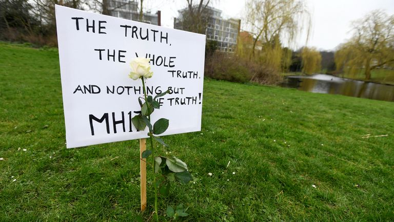 A placard calls for 'the whole truth'