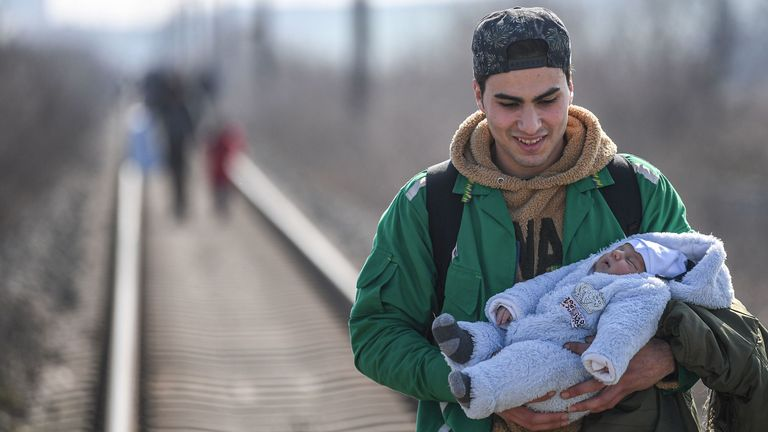 A migrant carries his baby