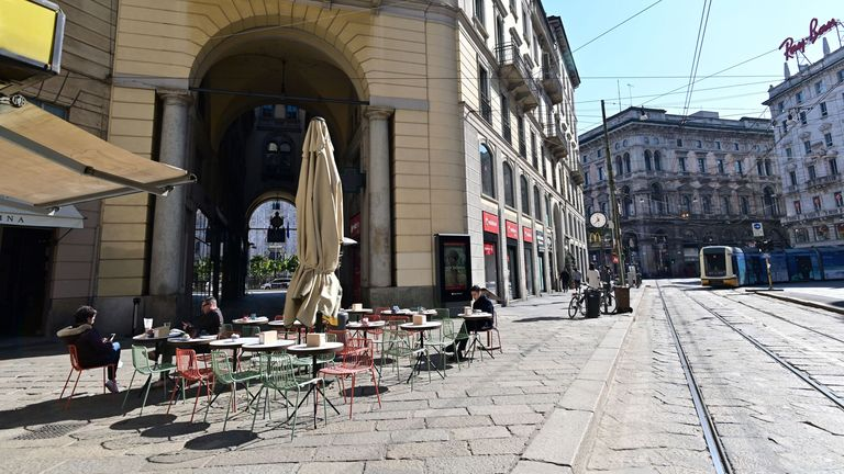 Tourists sit at a cafe terrace in central Milan
