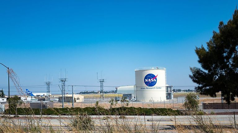 Storage tank with logo for NASA Ames Research Center, with Moffett Field visible in the background, in the Silicon Valley town of Mountain View, California, August 25, 2016. (Photo via Smith Collection/Gado/Getty Images).