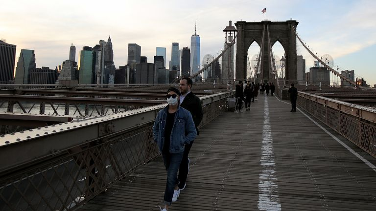A pedestrian in a protective face mask walks across the Brooklyn Bridge