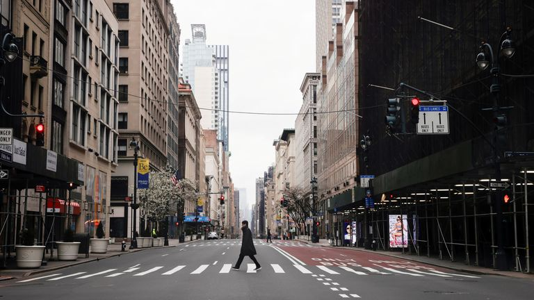 A man crosses a nearly empty 5th Avenue in midtown Manhattan