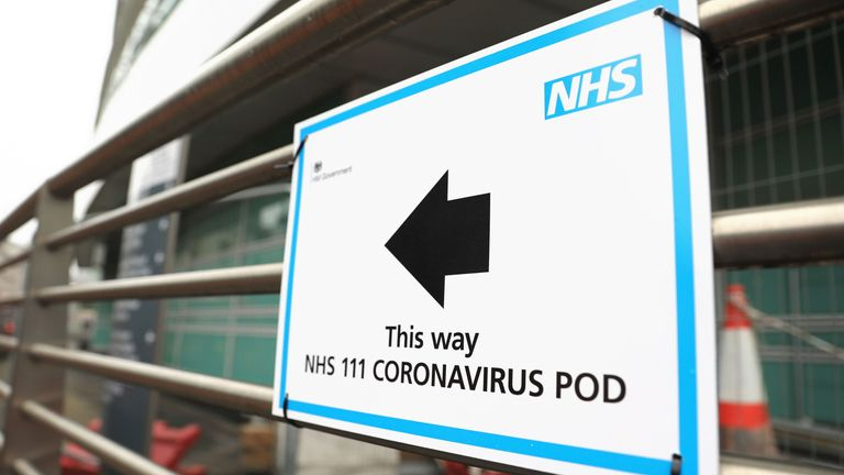 A sign directs patients towards an NHS 111 coronavirus pod at a UK hospital.