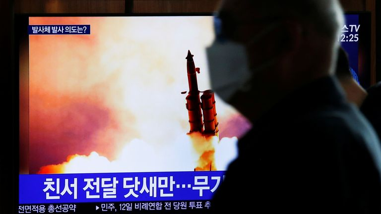 A man walks past a TV broadcasting file footage for a news report on North Korea firing an unidentified projectile
