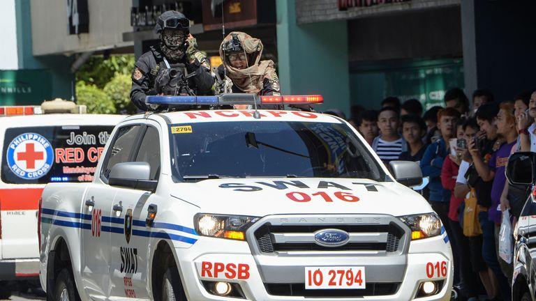 Armed members of a police SWAT team stand in the back of a truck near the mall in Manila