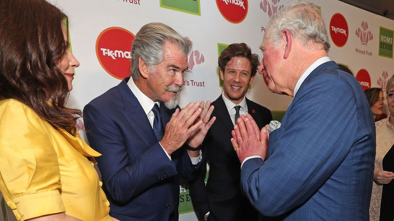 LONDON, ENGLAND - MARCH 11: Prince Charles, Prince of Wales uses the Namaste gesture to greet Anna Friel and Pierce Brosnan as he attends the Prince's Trust And TK Maxx & Homesense Awards at London Palladium on March 11, 2020 in London, England. (Photo by Yui Mok - WPA Pool/Getty Images)