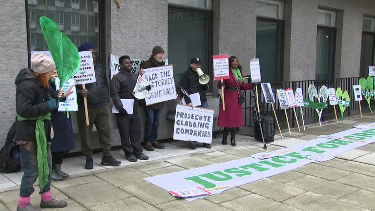 Protesters stand outside the Grenfell inquiry