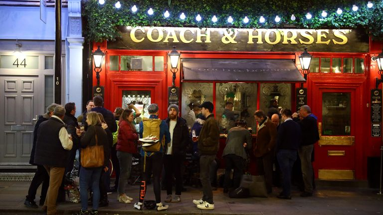 People stand outside a pub in Soho on Tuesday
