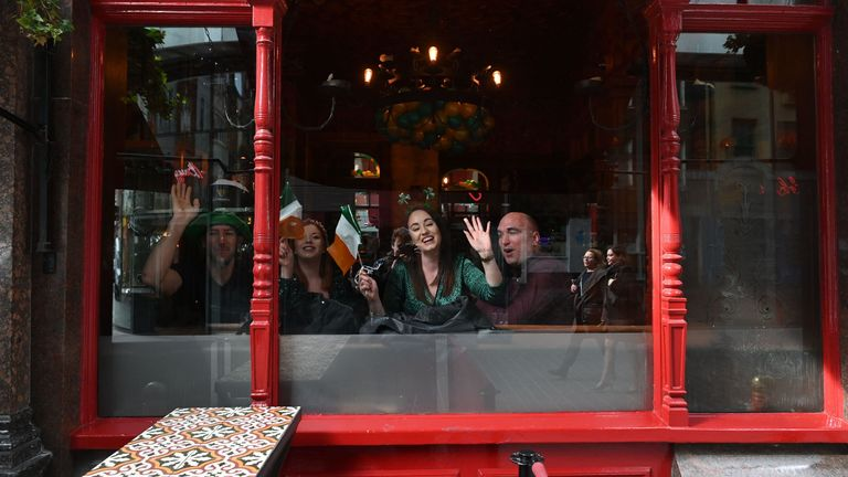 Revellers look out of the window of an Irish pub as they celebrate St Patrick's Day in central London on March 17