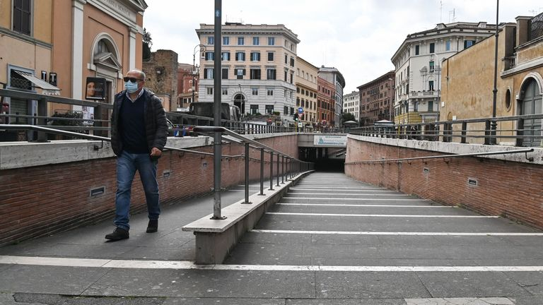 A person wearing a respiratory mask walks across a deserted Vatican underpass near ST. Peter Basilica, in central Rome on March 15, 2020, during the COVID-19 outbreak caused by the novel coronavirus. (Photo by Andreas SOLARO / AFP) (Photo by ANDREAS SOLARO/AFP via Getty Images)