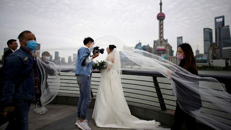 Staff members wearing face masks help a couple with their wedding photo shoot in Shanghai