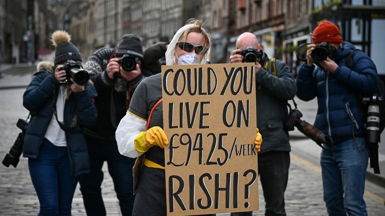 A woman wearing a mask, holds a sign which asks Chancellor Rishi Sunak if he could live on the statutory sick pay rate for employees £94.25 per week on March 23, 2020 in Edinburgh, Scotland
