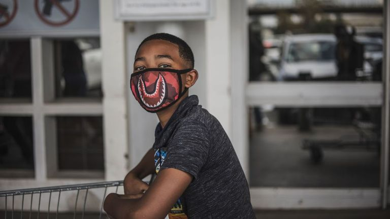 A boy wears a face mask as a preventive measure against the spread of the COVID-19 coronavirus as he queues outside Makro in Soweto, Johannesburg