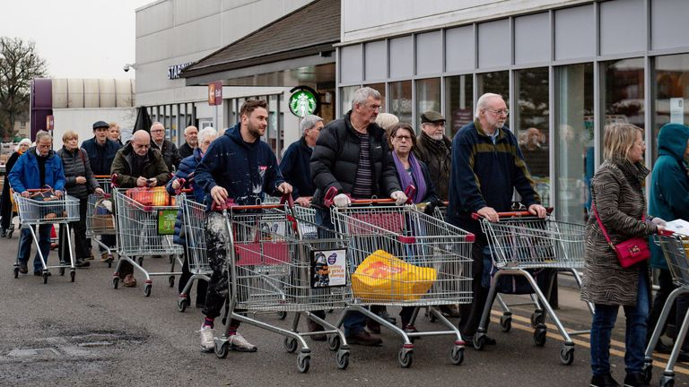 Shoppers queue outside a Sainsbury's supermarket in Leamington Spa
