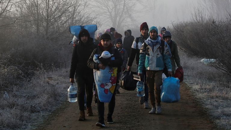 Migrants walk along the Evros river to reach Greece, near the Turkish border city of Edirne, Turkey
