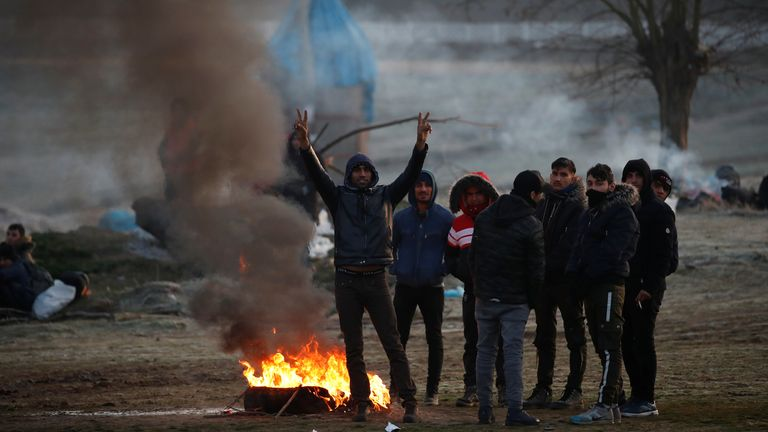Migrants gather around a fire as they wait to cross the Evros river to reach Greece