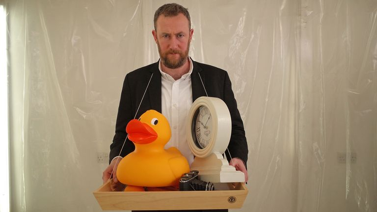 Taskmaster - Series 9 - Episode 04.Picture shows: Alex Horne holding David's attempt of the Tray Task..Tray Task: Say a letter of the alphabet. You have ten seconds. Your time starts now. Put the most things beginning with the letter you just said on this tray. .The tray may not leave Alex and Alex may not leave the lab. Most things beginning with the letter you just said on the tray in five minutes from now wins. Credit: Andy Devonshire