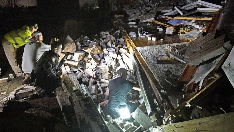 Rescuers work freed a couple from the rubble of their home home in Mt. Juliet, Tennessee