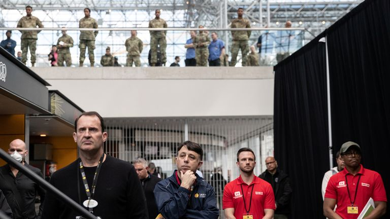 US Army and Javit center personnel stand apart while looking on as New York Governor Andrew Cuomo speaks