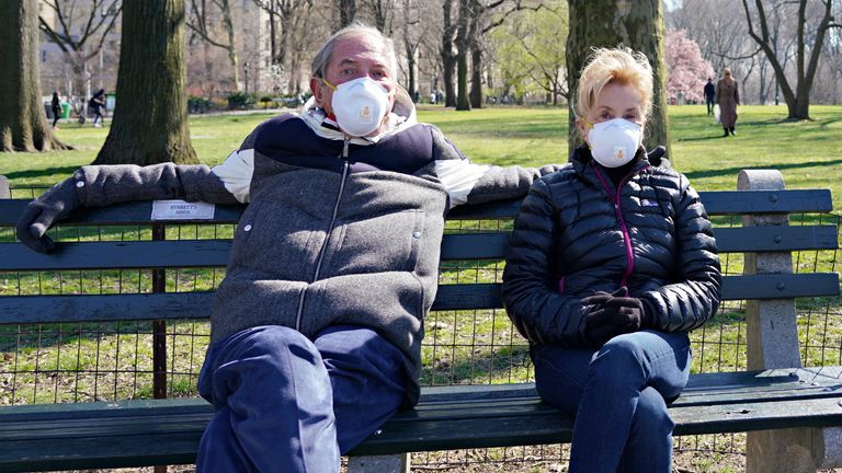 A man and woman wear protective masks in Central Park as the coronavirus continues to spread across the United States on March 26, 2020 in New York City