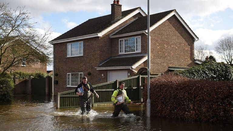 Local people go door to door collecting belongings and helping residents in the rising floodwaters in East Cowick